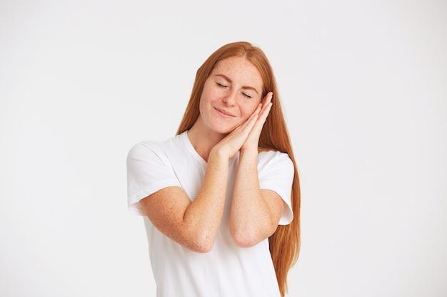 長い赤い髪とそばかすのある驚くべき素敵な若い女性のクローズアップはtシャツを着ています