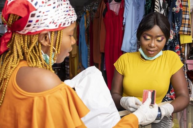 ラテックス手袋とお店でクレジットカードで支払うフェイスマスクを持つアフリカの女性のクローズアップ