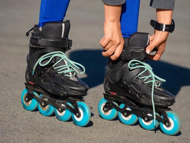 스케이트를 타기 전에 롤러 블레이드에 끈을 고정하는 익명의 여자 손 클로즈업