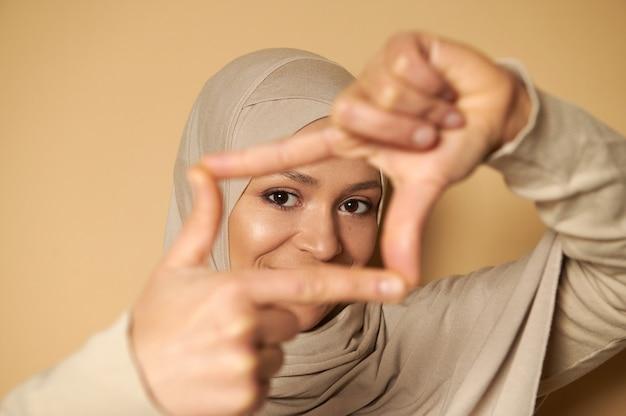 指フレームを通してヒジャーブの美しいアラブのイスラム教徒の女性の魅力的な外観のクローズアップ