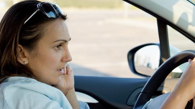 자동차의 스티어링 휠 뒤에 sittting 매력적인 유행 여자의 근접 촬영