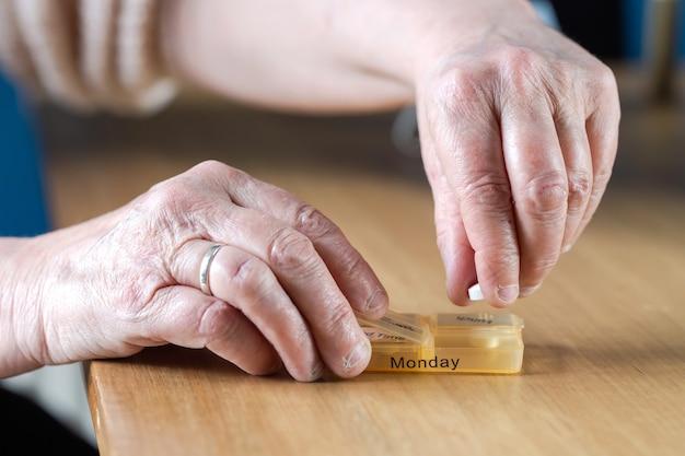 木製のテーブルbusinesshealthコンセプトのピルボックスで1週間彼女の薬を服用している年配の年配の女性の手のクローズアップ