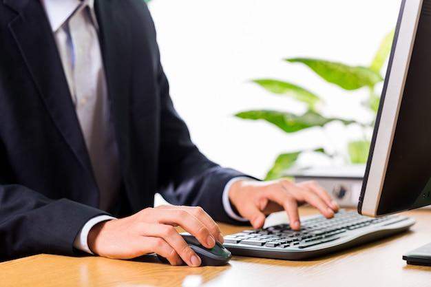 Крупный план сотрудника, печатающего на клавиатуре и держащего мышь