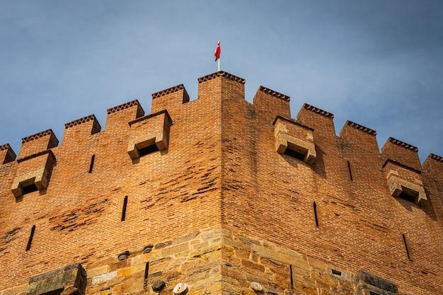 Крупный план старой красной башни с флагом туриец. верфь и арсенал в алании в яркий солнечный день, турция