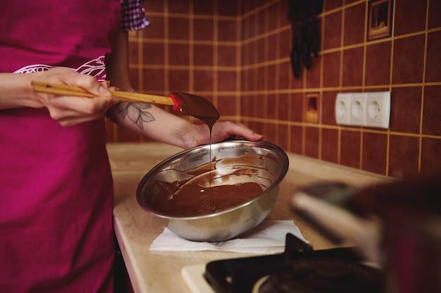 그녀의 집 부엌에 서있는 나무 주걱으로 그릇에 녹은 초콜릿 덩어리를 혼합하는 분홍색 앞치마에 인식 할 수없는 과자 장의 근접 촬영