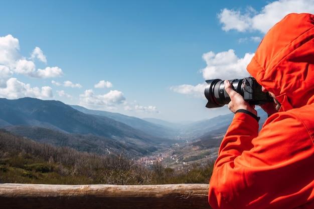 Крупный план неузнаваемого фотографа, делающего снимок горного пейзажа с копией пространства