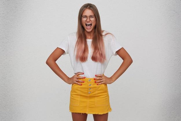 怒っている狂気の若い女性のクローズアップはtシャツ、黄色のスカートを着て、眼鏡は腰に手を保ち、白い壁の上に孤立して叫ぶ