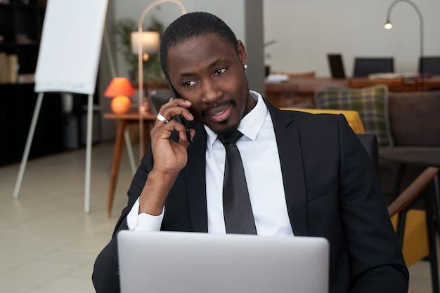 Крупный план сердитого молодого африканского человека кричащего пока говорящ на smartphone