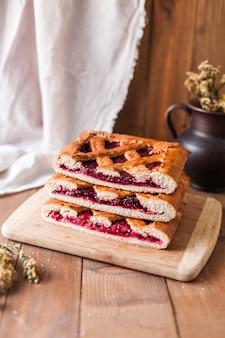 Крупный план аппетитного типичного русского фаршированного сладкого ягодного пирога, выложенного белой тканью