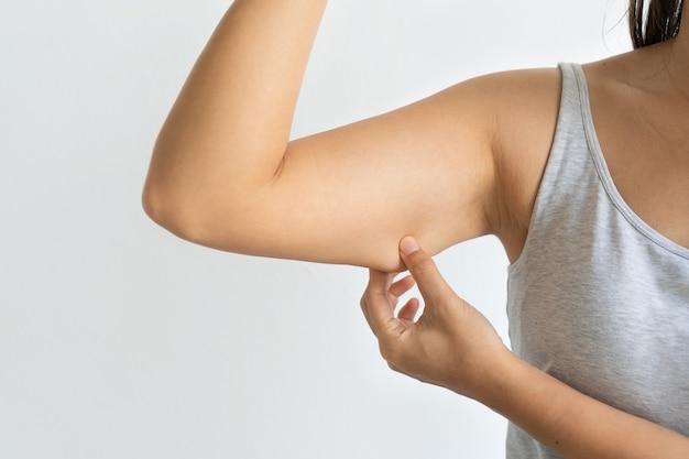 팔 지방 연약한 피부를 꼬집는 아시아 여자의 근접 촬영, 여성 당기는 과도한 지방