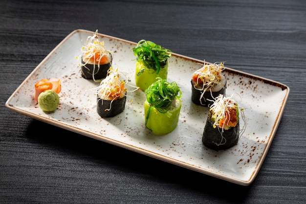 어두운 배경, 전형적인 일본 음식에 다양한 스시 롤을 닫습니다.