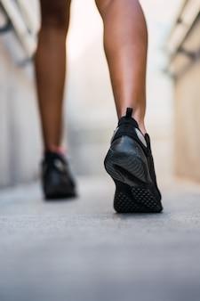 実行し、屋外で運動をしている運動選手の女性のクローズアップ。スポーツと健康的なライフスタイル。