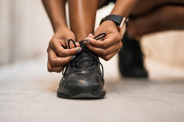 彼女の靴ひもを結び、屋外での作業の準備をしているアスリート女性のクローズアップ。