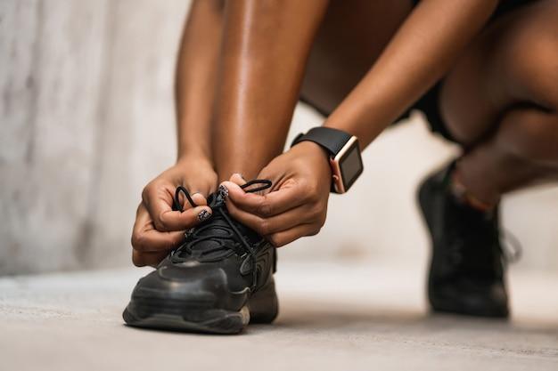 그녀의 구두 끈을 묶고 야외에서 운동을 준비하는 선수 여자의 근접 촬영