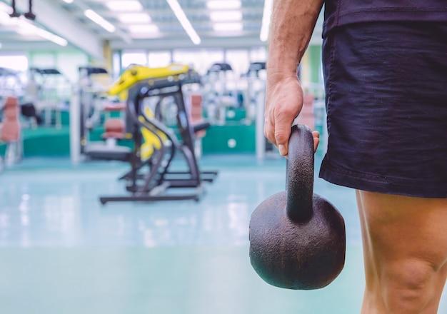 フィットネスセンターでのクロスフィットトレーニングで黒い鉄のケトルベルを保持している運動選手のクローズアップ