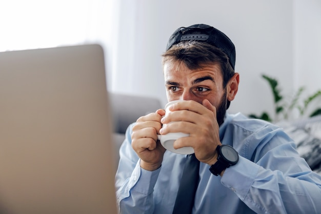 Крупным планом привлекательный бородатый бизнесмен, одетый в элегантную повседневную одежду, сидит дома, пьет кофе и смотрит на ноутбук.