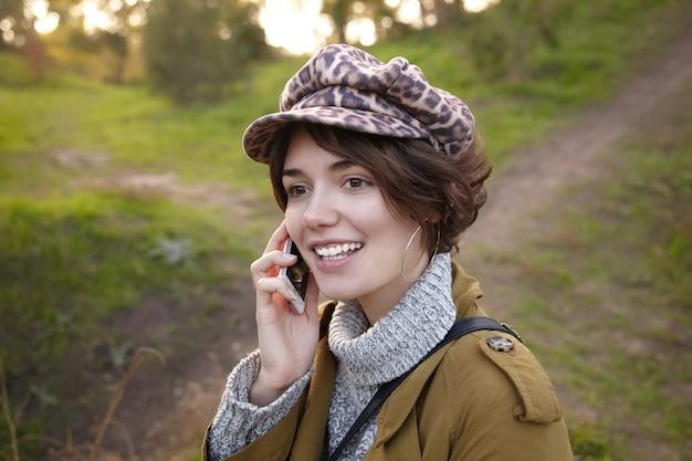 魅力的な茶色の目の若いブルネットの女性のクローズアップは、週末に公園を歩いている間、彼女の耳の近くにスマートフォンを保持しているヒョウ柄の帽子をかぶっています