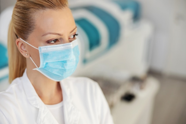 顔に保護マスクを付けて実験室に立っている魅力的な女性の実験室助手のクローズアップ。 covid発生の概念。