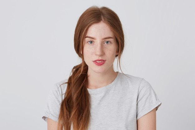 そばかすのある魅力的な平和的な赤毛の若い女性のクローズアップは自信を持っています