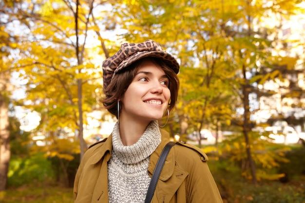 スタイリッシュなウェアでぼやけた公園の上でポーズをとっている間、脇を見て少し笑っているナチュラルメイクの魅力的なポジティブな若い茶色の髪の女性のクローズアップ