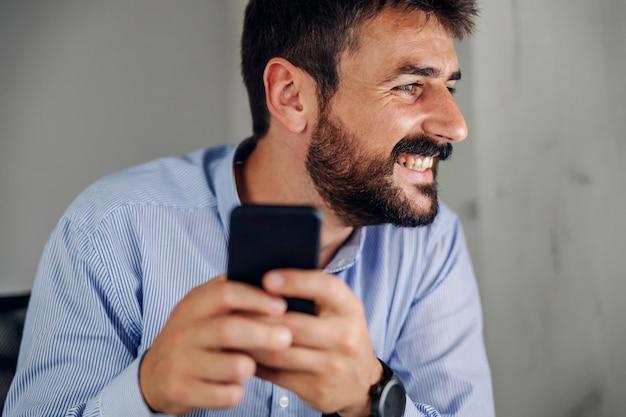 スマートフォンを保持している魅力的な笑顔のひげを生やした実業家のクローズアップ。
