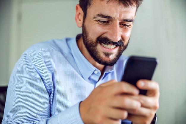 スマートフォンを保持している魅力的な笑顔のひげを生やしたビジネスマンのクローズアップ。