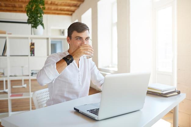 魅力的な青年実業家のクローズアップは、オフィスで白いシャツを着ています
