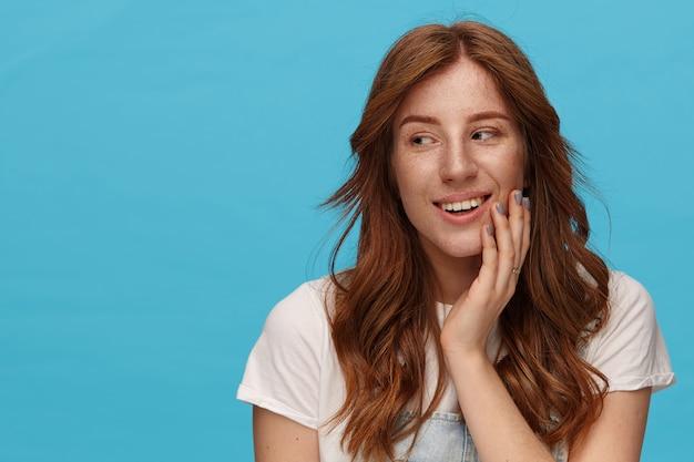 Крупным планом привлекательная молодая рыжая дама смотрит позитивно в сторону с легкой улыбкой и нежно трогает ее лицо поднятой рукой, изолированные на синем фоне