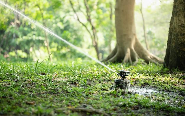 Крупный план автоматического полива спринклера в саду.