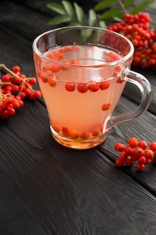 黒い木製のテーブルに赤いナナカマドと秋の飲み物のクローズアップ。
