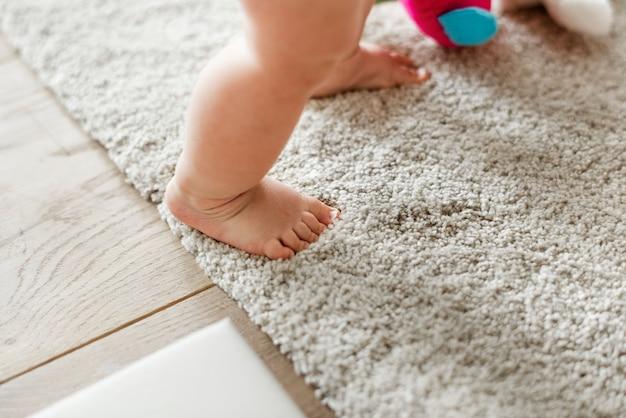 立っている間の赤ちゃんの足のクローズアップ