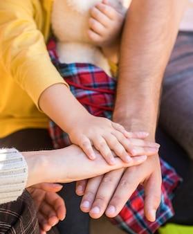 両親の手に赤ちゃんの手のクローズアップ。団結、サポート、保護、幸福の概念。親への子供の手のクローズアップ。父、母の手は、小さな赤ちゃんの手を保ちます。両親は赤ちゃんの手を握ります