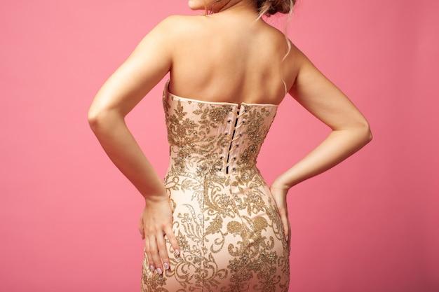 Крупный план спины сияющего бежевого вечернего платья с корсетом и шнуровкой на модели, изолированной на розовой спине ...