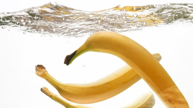 澄んだ水に落ちるバナナのクローズアップ