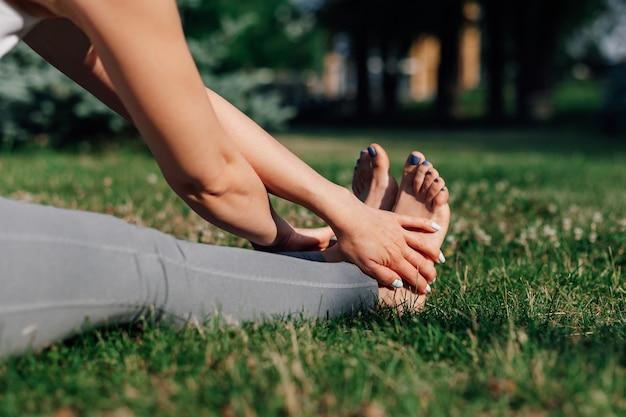 Крупным планом босые женские ноги растягиваются в парке на лужайке, наклоняясь вперед йоги утром летом