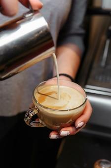 Крупным планом бариста наливает молоко в капучино или латте.