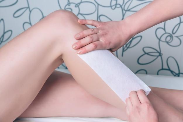 Крупным планом руки косметолог делают депиляцию ног красивой женщины с восковой полоской в салоне красоты