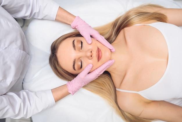 젊은 여자의 얼굴 성형 수술 개념 얼굴을 만지고 장갑에 미용사의 손의 근접 촬영