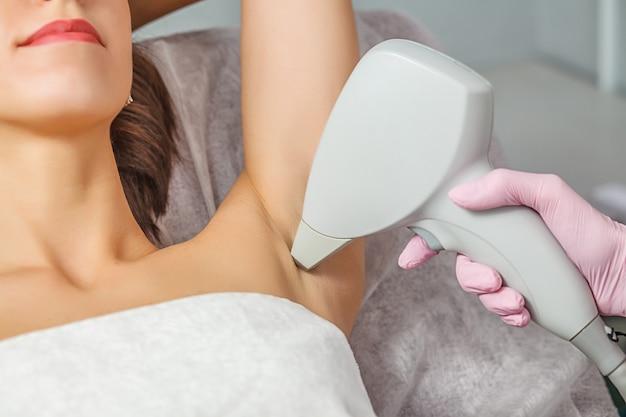 Макрофотография косметолога, удаляющего волосы подмышки женщины