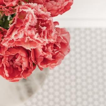 大理石のテーブルとモザイクタイルに美しいピンクの牡丹チューリップの花の花束のクローズアップ。