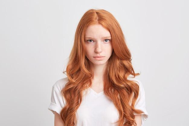 Крупным планом красивая рыжая молодая женщина с волнистыми длинными волосами и веснушками носит футболку грустно и смотрит вперед, изолированную над белой стеной