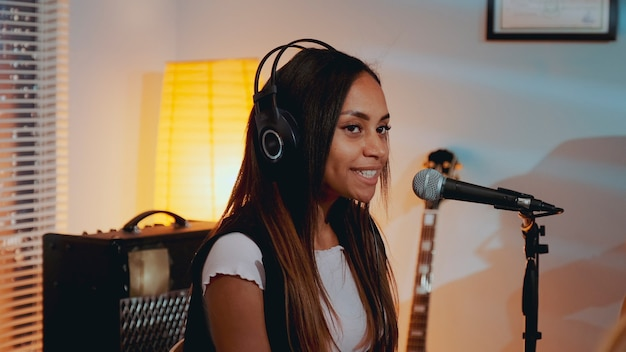 리허설에서 그녀가 좋아하는 노래를 부르는 헤드폰을 끼고 웃고 있는 아름다운 소녀의 근접 촬영