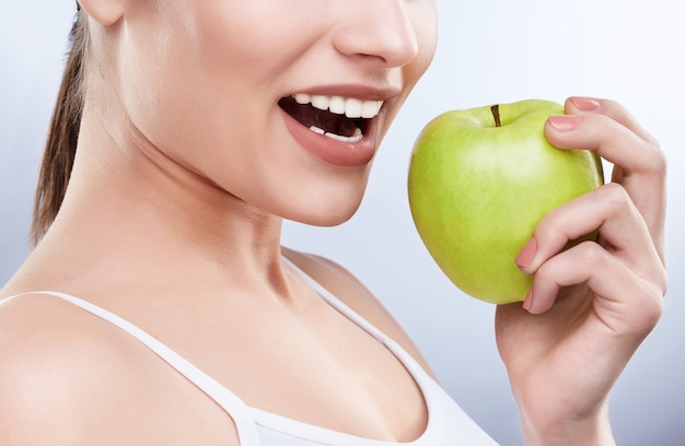 美しい真っ白な笑顔のクローズアップ。理想的な強い白い歯、歯のケア。ヘルスケア、歯科医のための口腔病学の概念。笑顔だけで、青リンゴを口の近くに持って、噛む準備ができています