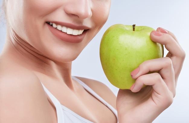美しい真っ白な笑顔のクローズアップ。理想的な強い白い歯、歯のケア。ヘルスケア、歯科医のための口腔病学の概念。青リンゴを口の近くに持って、笑顔だけ