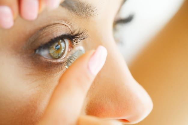 目の目のレンズを適用する美しい女性のクローズアップ