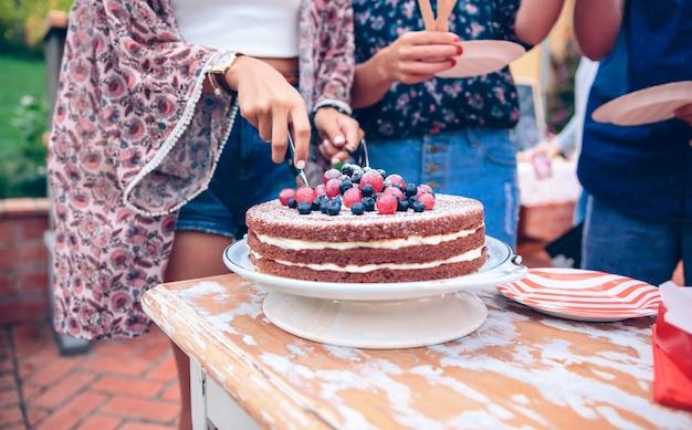 クリームとベリーで裸のチョコレートケーキを切る美しい女性と屋外の夏のパーティーで食べるためにプレートで待っている彼らの友人のクローズアップ
