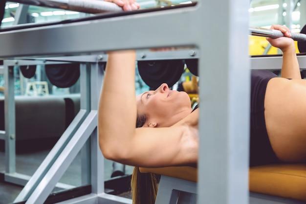 フィットネスセンターでベンチプレストレーニングでバーベルとエクササイズをしている美しい女性のクローズアップ