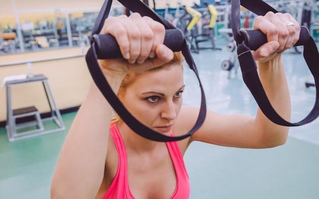 フィットネスセンターでフィットネスストラップを使用してハードサスペンショントレーニングを行っている美しい女性のクローズアップ。健康的でスポーティーなライフスタイルのコンセプト。