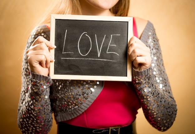 Крупным планом красивая женщина, держащая доску со словом «любовь», написанным мелом
