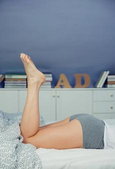 寝室の背景の上のベッドに横たわっている美しい女性の脚のクローズアップ